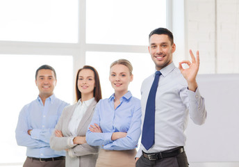 smiling businessman showing ok-sign in office