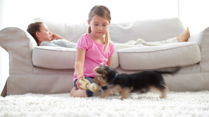 Little girl playing with puppy and bone with her mother reading