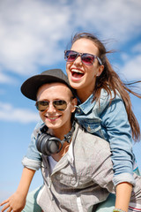 smiling teenagers in sunglasses having fun outside