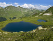 two lakes in the mountains with grass and flowers