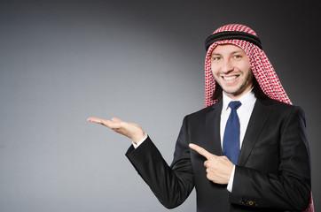 Arab businessman handing hands  againt grey background