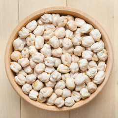 Chickpeas in wooden bowl, on wooden kitchen table