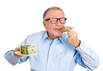 Hungry for money. Senior man holding plate full of cash, smells