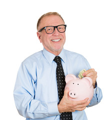 Savings in old age. Happy senior man holding piggy bank