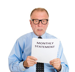 Expenses. Senior man shocked looking on monthly bank statement