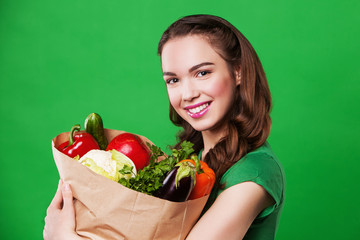 Young woman with a paper bag of vegetables. on green background.