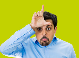 Bully guy giving Loser hand gesture on green background