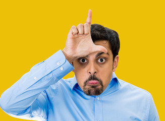 Bully guy giving Loser hand gesture on yellow background