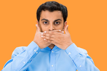 Speak no evil, man covering mouth, orange background