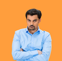 Portrait of Grumpy, difficult young man on orange background