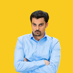 Portrait of Grumpy, difficult young man on yellow background