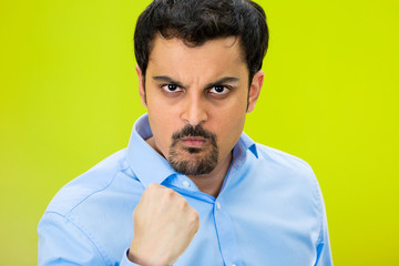 Portrait angry man with fist up, isolated green background