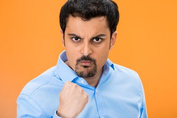 Portrait angry man with fist up, isolated orange background