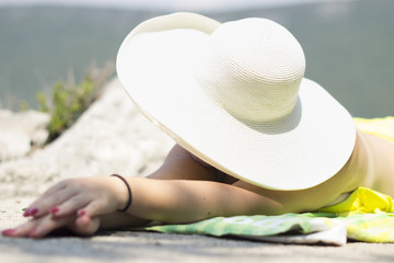 Woman sunbathing in a hat - summer vacation beach