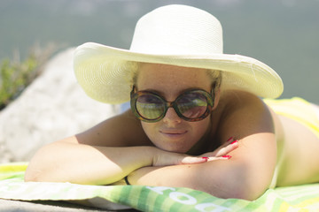 Happy vacation - summer woman sunbathing in a big hat