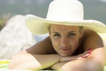 Woman sunbathing - vacation holidays & beach (portrait, hat)