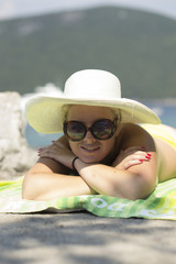 Blonde woman sunbathing topless (holidays, beach, vacation)