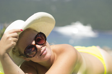 Woman sunbathing topless in a hat - Vacation, summer, holidays