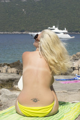 Blonde sunbathing topless - beach (yacht, holidays, vacation)