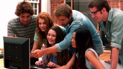 Happy students looking at computer
