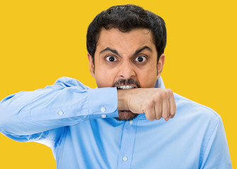 Crazy, upset young man Biting his arm, yellow background