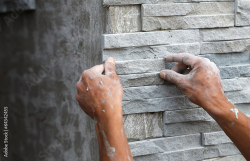 worker install stone wall surface with cement for house - 64342455