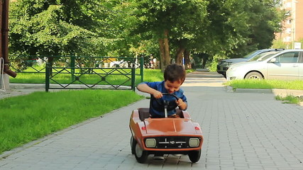 Three year old boy riding a toy car