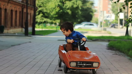 Cute little boy sits in a toy car and starts to go