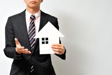 住宅を販売するスーツのビジネスマン