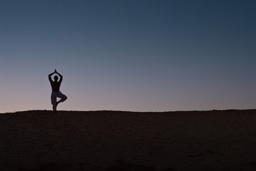 Male model practicing Yoga on the beach at sunset.