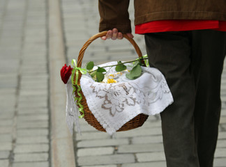 basket with dish covered with a placemat and a rose