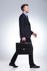 business man walks with suitcase