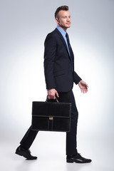 business man walks with suitcase in hand
