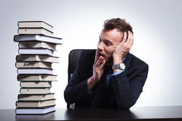 business man looks at pile of books