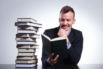 pensive business man smiles while reading