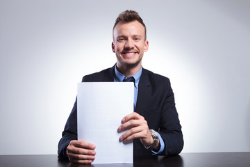 business man smiles holding documents