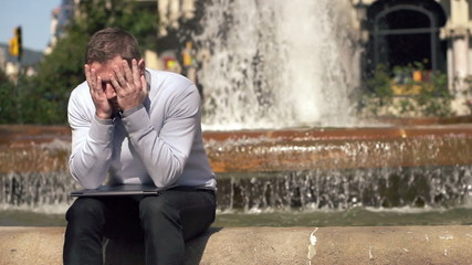 Businessman having headache in the city, super slow motion