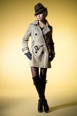 young girl in coat with hat walking on beige background