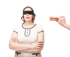 Blindfold plus size woman temptating with hamburger