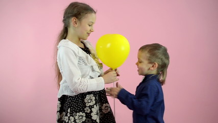 Little boy gives a girl a yellow balloon. Pink background.