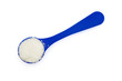 powdered milk in a blue spoon on white with clipping path