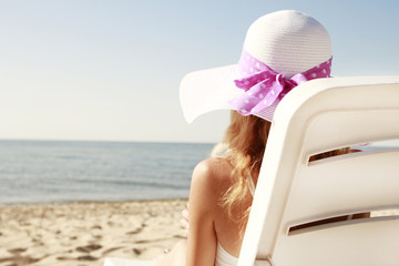 girl in hat is lying on a deck chair on the beach