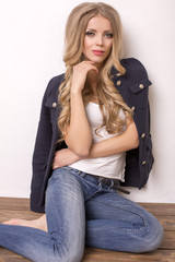 sexy woman with long blond hair in jeans and jacket