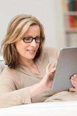 ältere frau liest zuhause am tablet-pc