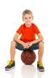 kid sitting on a basketball