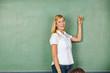 Lehrer in Schule zeigt mit Hand auf Tafel
