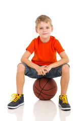 kid sitting on a basketball