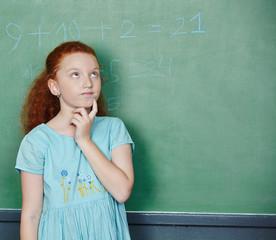 Mädchen löst Rechenaufgabe an Tafel