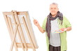 Mature artist drawing on an easel