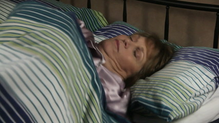 Middle aged woman lying in bed turns over in her sleep.